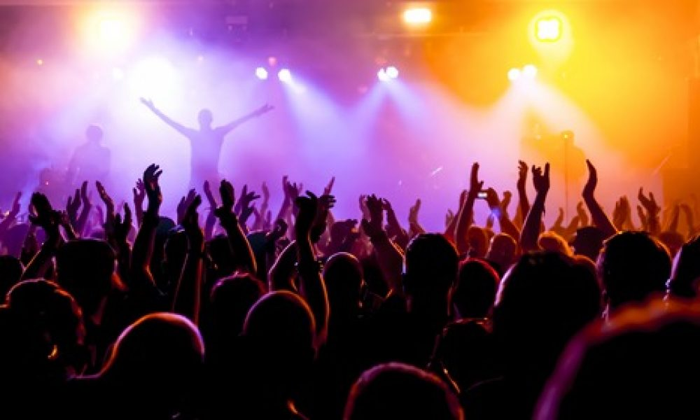 Silhouettes,Of,Concert,Crowd,In,Front,Of,Bright,Stage,Lights